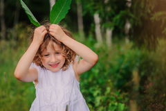 Child girl playing with leaves in summer forest with birch trees. Nature exploration with kids. Stock Photography