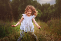 Child girl playing with leaves in summer forest. Nature exploration with kids Stock Photography
