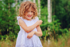 Child girl playing with leaves in summer forest. Nature exploration with kids Royalty Free Stock Images