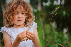Child girl playing with leaves in summer forest. Nature exploration with kids Royalty Free Stock Photography