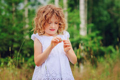 Child girl playing with leaves in summer forest. Nature exploration with kids Stock Photos