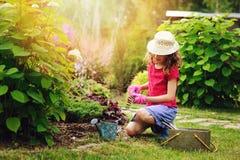 Child girl playing little gardener and helping in summer garden Stock Image