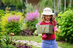 Child girl playing little gardener and helping in summer garden Stock Images