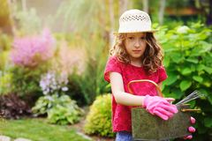 Child girl playing little gardener and helping in summer garden, wearing hat and gloves. Working with tools Royalty Free Stock Photography