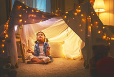 Child girl playing meditates in yoga pose in tent at home Royalty Free Stock Photography