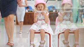 Child girl playing with a mobile phone in the shopping mall. Baby uses a game application on a smartphone.  stock footage