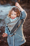 Child girl playing with pine cones on the walk in winter forest Stock Images