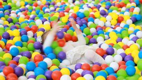Child girl playing on the playground with multicolored balloons. Baby plays games for children. Child girl playing on the playground with multicolored balloons stock video