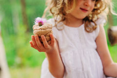 Child girl playing with salt dough cake decorated with flower Stock Image