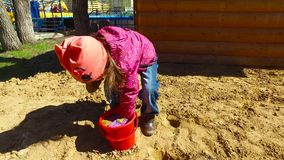 Child girl playing in the sandbox. Girl posing cake out of the sand. Sunny spring day in an urban public park. Closeup. Overlaying the wet sand in a bucket stock video