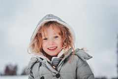 Child girl playing with snow on the walk in winter forest Royalty Free Stock Photo