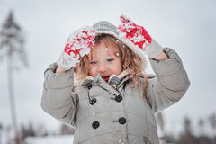 Child girl playing with snow on the walk in winter forest Stock Image