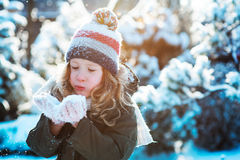 Child girl playing with snow in winter garden or forest, making snowballs and blowing snowflakes Royalty Free Stock Image