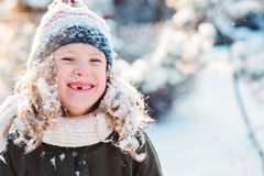 Child girl playing with snow in winter garden or forest, making snowballs and blowing snowflakes Royalty Free Stock Images
