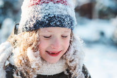 Child girl playing with snow in winter garden or forest, making snowballs and blowing snowflakes Royalty Free Stock Photo