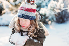 Child girl playing with snow in winter garden or forest, making snowballs and blowing snowflakes Stock Photos