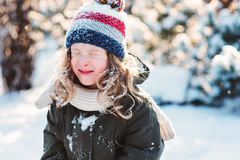 Child girl playing with snow in winter garden or forest, making snowballs and blowing snowflakes Stock Photography