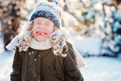 Child girl playing with snow in winter garden or forest, making snowballs and blowing snowflakes Stock Images