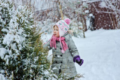 Child girl playing on snowy winter backyard Royalty Free Stock Photos