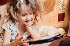 Child girl playing tablet at home Stock Photo
