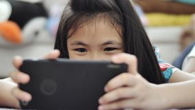Child girl playing tablet or smartphone at home ,. Asian girl playing game on mobile phone with smile face stock footage
