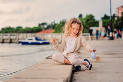 Child girl playing with toy bird on seaside on summer vacation with sea background Royalty Free Stock Images