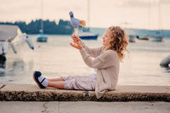 Child girl playing with toy bird on seaside on summer vacation Stock Photography