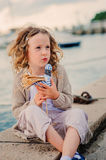 Child girl playing with toy bird on seaside on summer vacation Stock Images