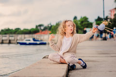 Child girl playing with toy bird on seaside on summer vacation Royalty Free Stock Images