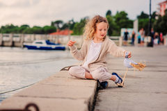 Child girl playing with toy bird on seaside on summer vacation in Slovenia Stock Image