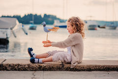 Child girl playing with toy bird on seaside on summer vacation in Slovenia Stock Photography