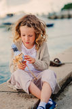 Child girl playing with toy bird on seaside on summer vacation Stock Image