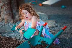 Child girl playing with toy shovel and wheelbarrow on playground Royalty Free Stock Image