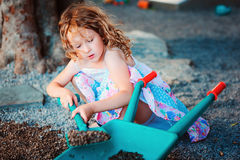 Child girl playing with toy shovel and wheelbarrow on playground Stock Image