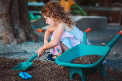 Child girl playing with toy shovel and wheelbarrow on playground Royalty Free Stock Images