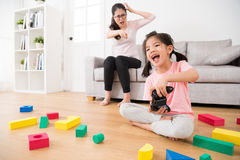 Child girl playing video games having fun. Cheerful pretty child girl playing video games having fun with controller and mad mother frustrating looking at and Royalty Free Stock Photo