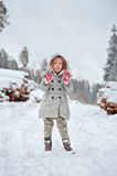 Child girl playing on the walk in winter snowy forest Stock Images