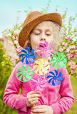 Child girl playing windmill in blooming garden. Five years old caucasian blond child girl in a hat playing windmill on blooming garden background. Spring Stock Images