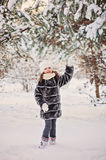Child girl playing in winter snowy forest Royalty Free Stock Images