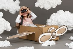 The child girl plays in an airplane made of cardboard box and dreams of becoming a pilot, clouds of cotton wool on a gray backgrou royalty free stock photos