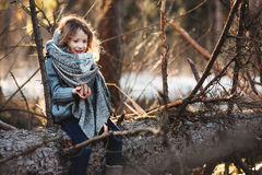 Child girl plays with pine cones on tree log in winter forest Royalty Free Stock Photos