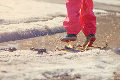 Child girl plays puddle jumping in early spring Stock Images