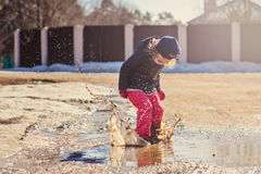 Child girl plays puddle jumping in early spring Royalty Free Stock Image