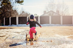 Child girl plays puddle jumping in early spring Stock Photo