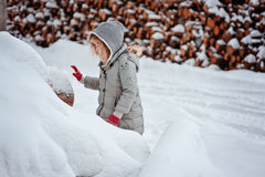 Child girl plays with snow on the walk in snowy winter Royalty Free Stock Photo