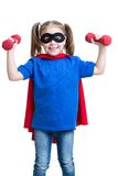 Child girl plays superhero and lifts dumbbells Stock Image