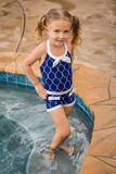 Child girl pool swim. Young female child in blue swim suit standing on pool steps royalty free stock image