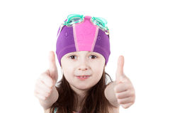 Child girl in pool swimming cap isolated on white background. Gesture of OK stock photography