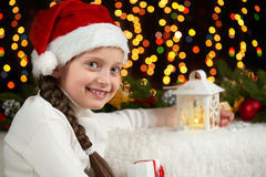 Child girl portrait with christmas decoration, dark background with lights, face expression and happy emotions, dressed in santa h Stock Image