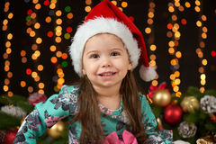 Child girl portrait in christmas decoration, happy emotions, winter holiday concept, dark background with illumination and boke li Stock Images